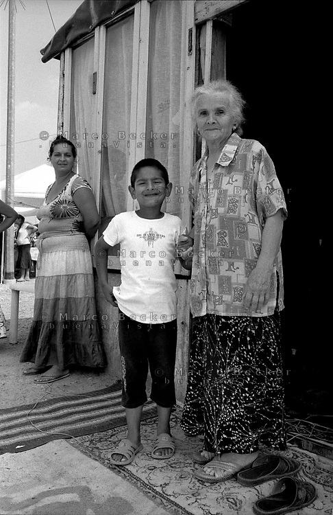 milano, periferia nord. campo di nomadi rom romeni di via triboniano. nonna e nipote e la madre sullo sfondo --- milan, north periphery. rumanian nomads camp of triboniano street. grandmother and grandson and the mother and the background