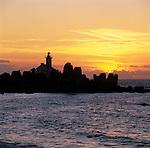 France, Brittany, near Brignogan Plage: Sunset behind Pointe de Pontusval Lighthouse.
