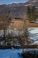 """Switzerland. Canton Ticino. Cureglia is a municipality in the district of Lugano. """"Tiratori del Gaggio"""" society. View on the shooting range from the targets distants 300 meters. Snow and trees in winter season. Car on the road. Snowy Alps.  9.02.2019 © 2019 Didier Ruef"""