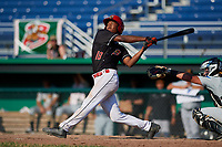 Batavia Muckdogs center fielder Brayan Hernandez (18) follows through on a swing in front of catcher Paul Brands (19) during a game against the West Virginia Black Bears on July 1, 2018 at Dwyer Stadium in Batavia, New York.  Batavia defeated West Virginia 8-4.  (Mike Janes/Four Seam Images)