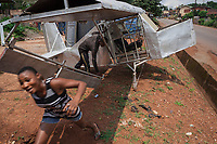 Nigeria. Enugu State. Amechi. The airplane's model was built by Michael Nweze during his free time in order to show to potential customers his craft in welding. Michael Nweze was assisted in his work by a fellow junior welder Daniel  who stands by the plane's door. A joyful woman is running away from the aircraft. 9.07.19 © 2019 Didier Ruef