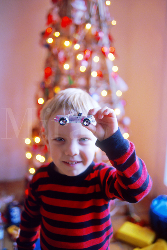 Child at Christmas looking up holding favorite toy car that he just unwrapped