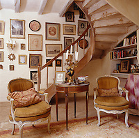 A wooden staircase curves up to the first floor from one end of the living room infront of a wall hung with an assortment of pictures