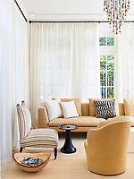 In the living room, the neutral background allows the contrast in forms and textures to shine and gives the room a chic simplicity.