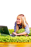 Beautiful blonde teen laying on a shag rug using a laptop computer.