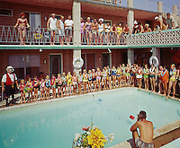 Kids pool party with a hawaiian theme and a man dressed up with large glasses. Moonlight Motel.