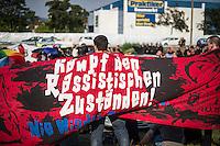 """Nach den pogromartigen Ausschreitungen gegen eine Fluechtlinsunterkunft im saechschen Heidenau am Freitag den 21. August 2015 durch Anwohnerinnen der Ortschaft, kamen am Samstag de 22. August 2015 ca. 250 Menschen in die Ortschaft um ihre Solidaritaet mit den Gefluechteten zu zeigen.<br /> Am Vorabend hatten Rassisten, Nazis und Hooligans sich zum Teil Strassenschlachten mit der Polizei geliefert um zu verhindern, dass Fluechtlinge in einen umgebauten Baumarkt einziehen. Ueber 30 Polizisten wurden dabei verletzt.<br /> Bis in die Abendstunden des 22. August blieb es trotz spuerbarer Anspannung um die Unterkunft ruhig. Im Laufe des Tages wurden immer wieder Gefluechtete mit Reisebussen gebracht was von den wartenenden Heidenauern mit Buh-Rufen begleitet wurde. Vereinzelt wurde auch """"Sieg Heil"""" gerufen, was die Polizei jedoch nicht verfolgte.<br /> Kurz vor 23 Uhr griffen Nazis und Hooligans dann wie am Vorabend die Polizei mit Steinen, Flaschen, Feuerwerkskoerpern und Baustellenmaterial an. Die Polizei mussten mehrfach den Rueckzug antreten, scheuchte den Mob dann von der Fluechtlingsunterkunft weg. Dabei wurden auch wieder Traenengasgranaten verschossen. Mindestens ein Nazi wurde festgenommen.<br /> Im Bild: Die antirassistische Kundgebung. Im Hintergrund der zur Erstaufnahme umgebaute Baumarkt.<br /> 22.8.2015, Heidenau<br /> Copyright: Christian-Ditsch.de<br /> [Inhaltsveraendernde Manipulation des Fotos nur nach ausdruecklicher Genehmigung des Fotografen. Vereinbarungen ueber Abtretung von Persoenlichkeitsrechten/Model Release der abgebildeten Person/Personen liegen nicht vor. NO MODEL RELEASE! Nur fuer Redaktionelle Zwecke. Don't publish without copyright Christian-Ditsch.de, Veroeffentlichung nur mit Fotografennennung, sowie gegen Honorar, MwSt. und Beleg. Konto: I N G - D i B a, IBAN DE58500105175400192269, BIC INGDDEFFXXX, Kontakt: post@christian-ditsch.de<br /> Bei der Bearbeitung der Dateiinformationen darf die Urheberkennzeichnung in den EXIF- und IPTC-Dat"""