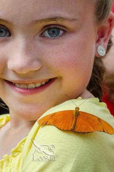 Cute girl with butterfly [Julia Butterfly (Dryas iulia)] on shoulder in butterfly garden.  No model release.