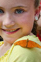 Cute girl with butterfly [Julia Butterfly (Dryas iulia)] on shoulder in butterfly garden.  No model release.