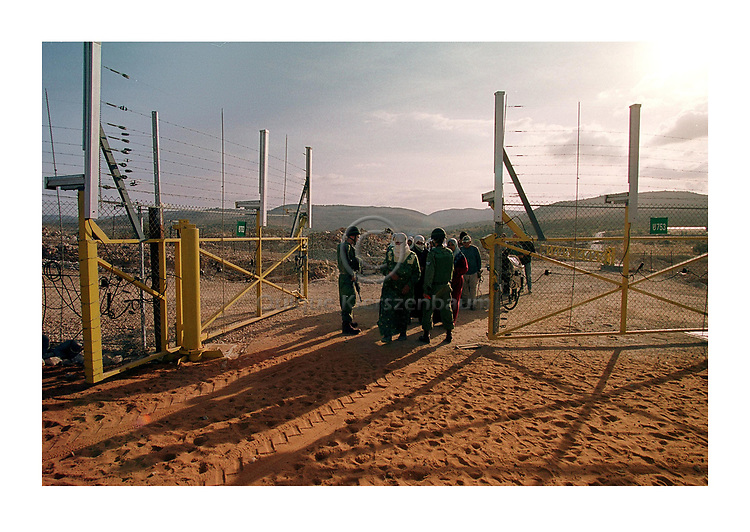 Israeli soldiers control the passage of Palestinian farmers to their land on the other side of the new separating fence in the Palestinian town of Jbareh to harvest the olive trees, October 28, 2004. According to Israeli army the gate was closed for the last ten days due to security reasons. Palestinian farmers have difficulties to harvest their olive trees due the new security conditions. Photo by Quique Kierszenbaum
