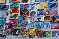 Colorful stickers advertising ice cold treats, spattered on the side of an ice cream truck parked near the playgroud of a public park.