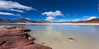 Volcanic stones and lagoon panorama of Salar de Aguas Calliente with the Láscar Volcano under a blue sky with white clouds, San Pedro de Atacama Chile