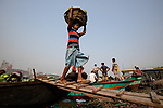 Workers unload thousands of colourful watermelons from boats at a bustling riverside market.  The largest of the boats can fit up to 500 melons, which are then carried in baskets balanced on the heads of the workers and loaded into delivery vans.<br /> <br /> The melons weigh between five and 20 kilograms, and each day up to 100,000 of the fruit are transported for sale at markets across Dhaka, the capital of Bangladesh.  SEE OUR COPY FOR DETAILS.<br /> <br /> Please byline: Azim Khan Ronnie/Solent News<br /> <br /> © Azim Khan Ronnie/Solent News & Photo Agency<br /> UK +44 (0) 2380 458800