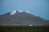 Mongolia, Bayan-Ulgii, Ulgii, Altai Mountains. Moon rising near Tsambagarav Mountain.