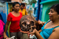 """A Mayan woman holds a dried-up scull of a deceased family member during the bone cleansing ritual at the cemetery in Pomuch, Mexico, 26 October 2019. Every year on the Day of the Dead, people of Pomuch, a small Mayan community in the south of Mexico, visit the cemetery to take part in a pre-Hispanic tradition of cleaning of bones of their departed relatives (""""Limpia de huesos""""). People who die in Pomuch are firstly buried for three years in an above-ground tomb then the dried-up bodies are taken out, bones are separated, wrapped in a decorated cloth, put into a wooden crate, and placed on display among flowers for veneration."""