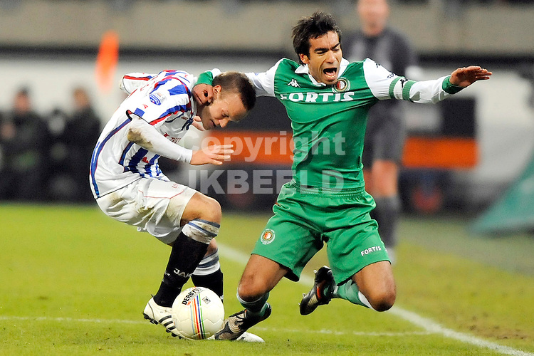 voetbal sc heerenveen - feyenoord eredivisie seizoen 2008-2009 16-01-2009 van bronkhorst onderuit tegen vayrynen. fotograaf jan kanning.