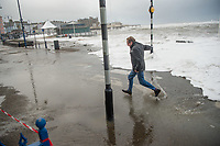 "Pictured: A man is caught up in water caused by waves that crash against the seaside town of Aberystwyth, Wales, UK. Saturday 21 October 2017<br /> Re: Coastal parts of the UK is facing winds of up to 70mph as Storm Brian causes roads to close and public transport to be cancelled.<br /> Roads in Aberystwyth's seafront and at nearby Aberaeron, Wales are shut on Saturday morning as a yellow ""be aware"" Met Office warning is in place.<br /> Seven flood warnings have been issued for the west Wales coast."
