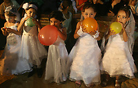 Palestinian girls are dressed up during a mass wedding party for grooms organized by the Islamic Association in the town of Beit Lahiya, northern Gaza Strip, Thursday, Aug. 16. 2007. The gathering marked the marriage for more than 50 men from the Islamic group Hamas.(photo by Fady Adwan""