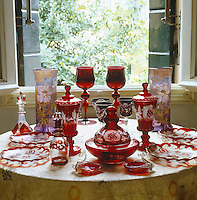 A collection of antique Bohemian red glassware is displayed on a table beside a pair of hand-painted Art Nouveau vases