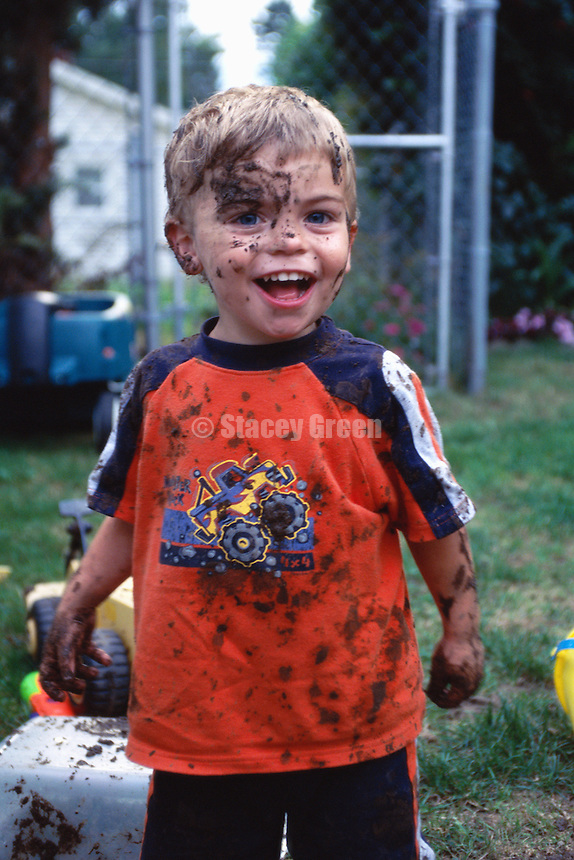 Boy (3-5) covered in mud