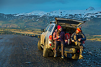 Male and female hikers sit on a tailgate of 4x4 vehicle with snow and glacier covered mountains in the background, Iceland