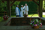 St Walstans Day, Bawburgh, St Mary and Saint Walstan's Church Norfolk 2018. Church members gather for Sunday church service and then process to the Holy healing well not far away.  <br /> <br /> Bishop Tony Foottit and Revd Penny Goodman, and ??? after the short service at the Holy Well.<br /> <br /> St Walstan dedicated his life to farming and the care of farm animals, he is the patron saint of saint of farm workers, farmers and farm animals. He died 30 May 1016, while at work in a meadow.