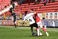 24th April 2021; The Valley, London, England; English Football League One Football, Charlton Athletic versus Peterborough United; Liam Miller of Charlton and Nathan Thompson of Peterborough tussle for the ball