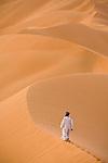 A man walks alone on the sand dunes of the Empty Quarter, Ar Rub Al Khali, Oman.