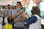 Palestinian students get inoculated with a dose of the Covishield vaccine against the Covid-19 coronavirus, at a school, in Nuseirat refugee camp in central Gaza Strip, on September 1, 2021. Palestinian health authorities are launching a vaccination drive for students aged 16-18 in the Gaza Strip as the territory contends with a third wave of coronavirus infections. Photo by Ashraf Amra