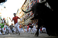 San Fermin, July 2012. Pamplona : Participants run with fighting bulls during a  San Fermin bull run in Pamplona on July 13, 2012. On each day of the San Fermin festival six bulls are released at 8:00 a.m. (0600 GMT) to run from their corral through the narrow, cobbled streets of the old navarre town over an 850-meter (yard) course. Ahead of them are the runners, who try to stay close to the bulls without falling over or being gored. Photo: Ander Gillenea.
