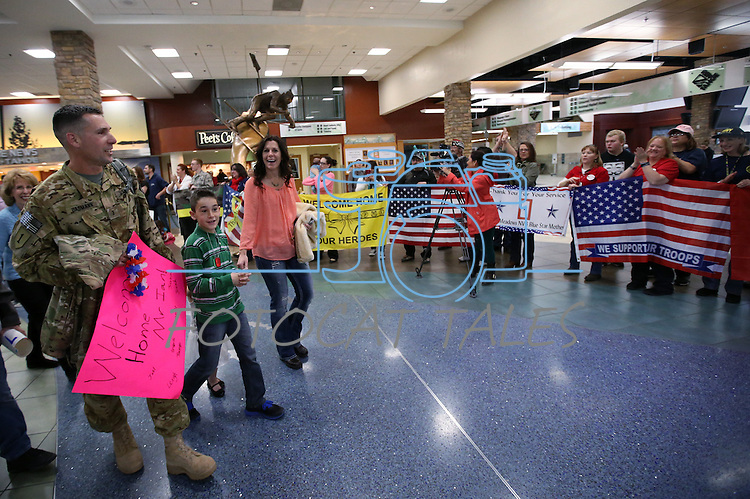 Chief Warrant Officer III Ian Dasmann and his family walk through the Reno-Tahoe International Airport in Reno, Nev., on Sunday, Feb. 16, 2014. About 300 supporters greeted the Nevada Army Guard soldiers after a 10-month deployment in Afghanistan. (Las Vegas Review-Journal/Cathleen Allison)