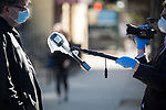 A reporter uses a microphone covered in plastic attached to a boom for an interview outside of Wyckoff Heights Medical Center during the coronavirus pandemic on April 6, 2020 in New York City.  More than 10,000 people have died from COVID-19 in the U.S..  Photograph by Michael Nagle
