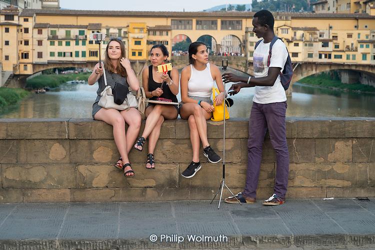 Unlicensed African street seller selling selfie sticks, Florence, Italy.