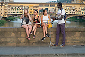 Unlicensed African street seller selling selfie sticks, Florence, Italy.