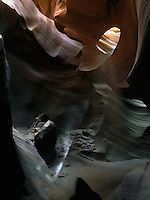A hooded spirit deep in the cavern of Lower Antelope Canyon in the Colorado Plateau near Lake Powell and Page Arizona