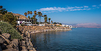 Fine Art Landscape Photograph of the Sea Of Galilee in Israel. White buildings and palm trees line the shoreline.