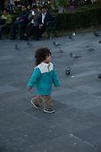 Arequipa, Peru. Peruvian child (girl, Peruvian) walking in public park; pigeons in background. No MR. ID: AL-peru.