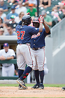 Cedric Hunter (27) of the Gwinnett Braves high fives teammate Adonis Garcia (18) after hitting a 2-run home run against the Charlotte Knights at BB&T BallPark on July 3, 2015 in Charlotte, North Carolina.  The Braves defeated the Knights 11-4 in game one of a day-night double header.  (Brian Westerholt/Four Seam Images)
