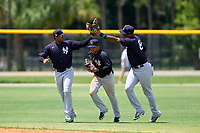 FCL Yankees outfielders Raimfer Salinas (31), Madison Santos (34) and Anthony Garcia (66) celebrate closing out a game against the FCL Tigers on June 28, 2021 at Tigertown in Lakeland, Florida.  (Mike Janes/Four Seam Images)