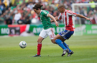 Andres Guardado (18) battles for possession ahead of Dario Veron (2). Mexico defeated Paraguay 3-1 at the Oakland Coliseum in Oakland, California on March 26th, 2011.