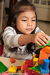 Education Preschool 3 year olds girl building block tower with colorful wooden blocks with different shapes