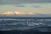 Mount Susitna is lit by morning sun behind the Anchorage skyline and U-Med district.