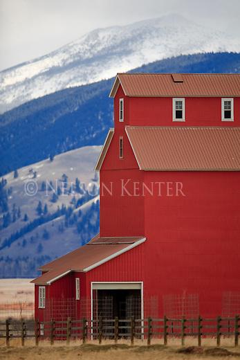 Red barn and snowy mountains near Ovando, Montana