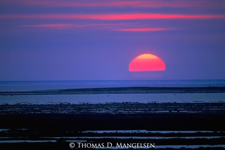 The view from Knight's Hill as the sun dips below the horizon in Hudson Bay, Churchill, Manitoba, Canada.