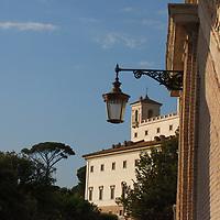 A view in the distance of the facade of Villa Medici, with a lamp in foreground and a pine on the background (Rome, 2020).<br /> <br /> Una vista da lontano della facciata di Villa Medici, con un lampione in primo piano ed un pino sullo sfondo (Roma, 2020.)