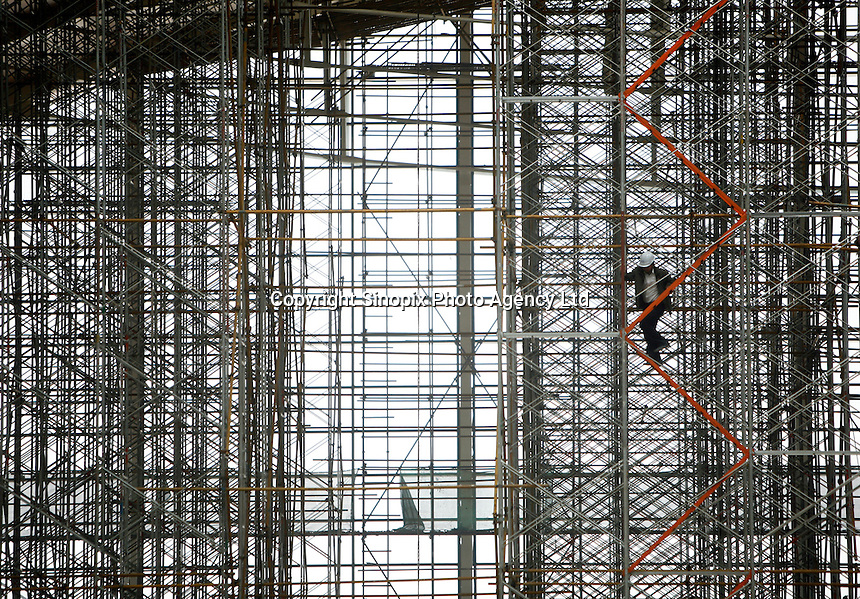 A worker climbs a scaffolding at the nearly-completed new terminal of the Pudong Airport expansion project in Shanghai, China..12 Mar 2007