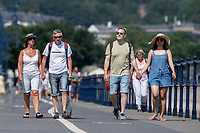WEATHER PICTURE WALES<br /> Pictured: People walk down the seafront in Mumbles, near Swansea, Wales, UK. Thursday 22 July 2021<br /> Re: High temperatures and sunshine has been forecast for most of the UK.