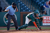 Greensboro Grasshoppers catcher Will Banfield (18) grabs the baseball as home plate umpire Josh Gilreath looks on during the game against the West Virginia Power at First National Bank Field on August 9, 2018 in Greensboro, North Carolina. The Power defeated the Grasshoppers 5-3 in game one of a double-header. (Brian Westerholt/Four Seam Images)