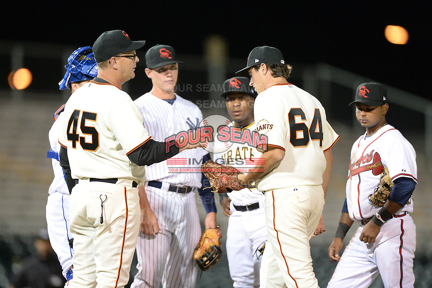 Scottsdale Scorpions manager Russ Morman (45), of the San Francisco Giants organization, hands the ball to Derek Law during a pitching change as Peter O'Brien, Gift Ngoepe, Elmer Reyes, and Angel Villalona look on during an Arizona Fall League game against the Salt River Rafters on October 9, 2013 at Scottsdale Stadium in Scottsdale, Arizona.  Salt River defeated Scottsdale 12-2.  (Mike Janes/Four Seam Images)