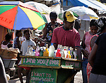 """Selling shaved ice, a man navigates his cart through the largest """"tent city"""" of Haitian earthquake survivors, located on a former nine-hole golf course in Port-au-Prince. The Petionville Club is host to more than 44,000 people.."""